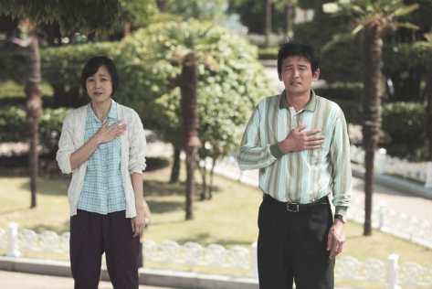 """Kontrowersyjna scena z """"Ode to Father"""", w której bohaterowie zaprzestają kłótni małżeńskiej, kiedy trzeba oddać hołd przy hymnie"""