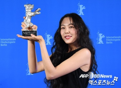 "South Korean actress Kim Min-hee poses with the Silver Bear award for best actress Bear in the movie ""Bamui haebyun-eoseo honja"" (On the Beach at Night Alone) during the Award Ceremony of the 67th Berlinale film festival in Berlin on February 18, 2017. / AFP PHOTO / POOL / Britta Pedersen"